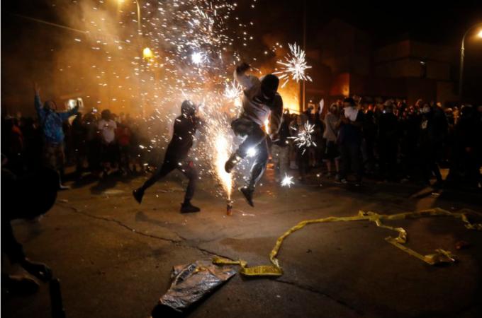 """<p class=""""Normal"""">Người biểu tình đốt pháo khi khu vực đồn cảnh sátMinneapolis bốc cháy. Các tòa nhà lân cận cũng chìm trong biển lửa.</p>"""