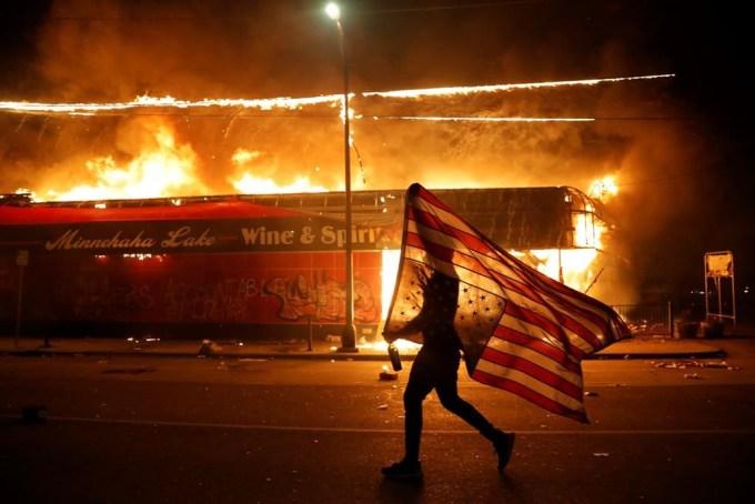"""<p class=""""Normal"""">Một người biểu tình mang lá cờ Mỹ lộn ngược, biểu hiện cho sự đau khổ, chạybên ngoài đồn cảnh sát.</p>"""