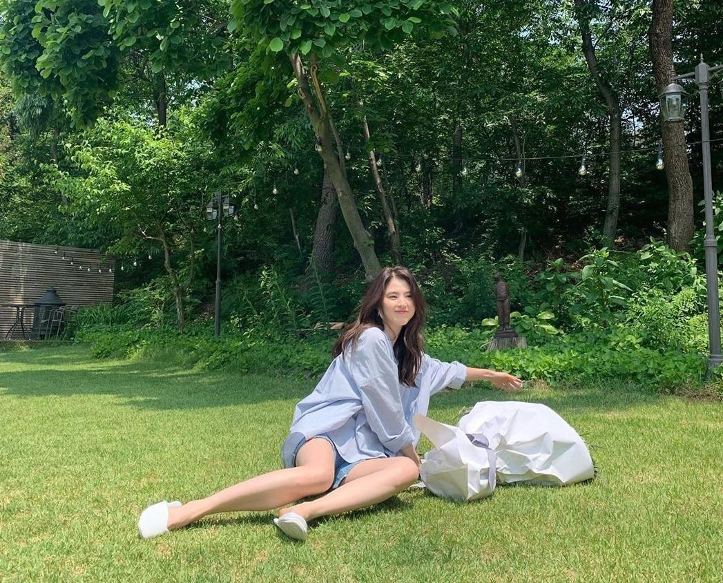 Han So Hee khoe chân dài khi vui đùa trên thảm cỏ.