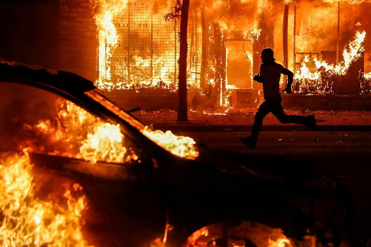 Một người biểu tình chạy qua tòa nhà đang cháy trên Đại lộ Chicago, ở Minnesota ngày 30/5. Ảnh: AP.