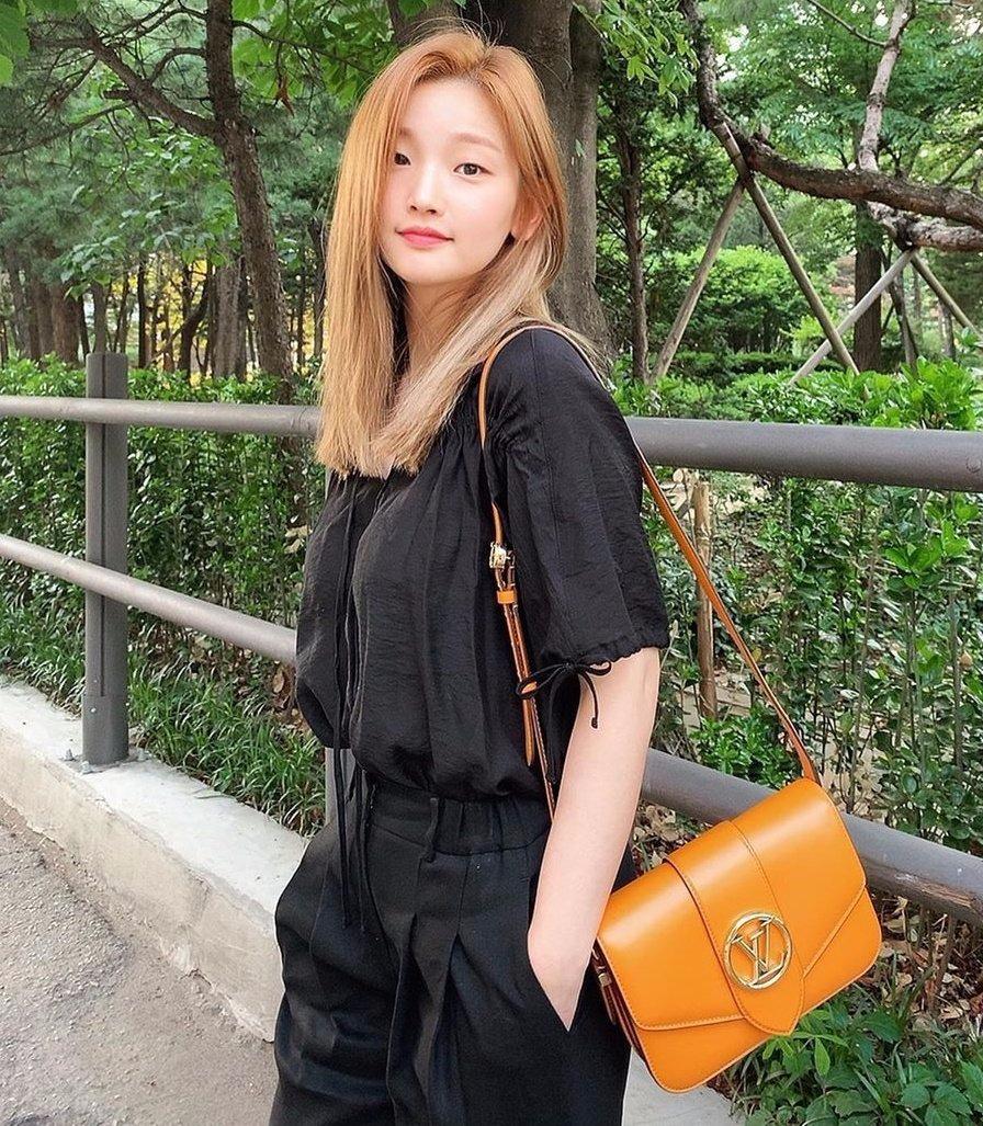 Nữ diễn viên Ký sinh trùng Park So Dam diện bộ cánh màu đen, làm nền cho chiếc túi tông vàng cam thêm nổi bật.