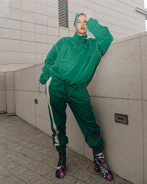 Cây đồ thể thao theo mốt sporty, tông xuyệt tông với mái tóc xanh lét của Quỳnh Anh Shyn trông không hề tệ, sai lầm của cô nàng nằm ở cách chọn đôi boots quá nặng nề, khiến đôi chân trông như ngắn lại, thân hình cục mịch hơn.
