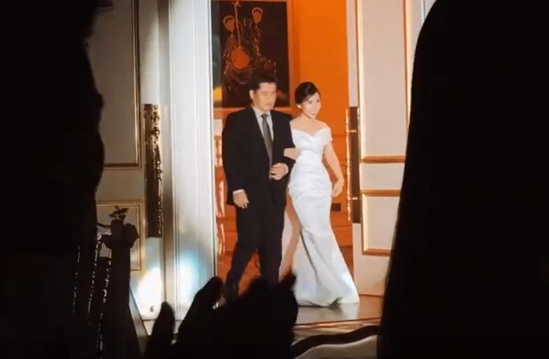 Viên Minh cùng bố tiến vào hôn trường trong chiếc váy trắng.