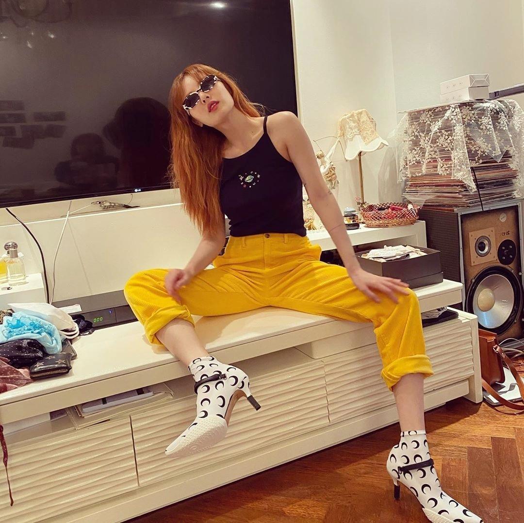 Hyuna đeo kính đen, ngồi dạng chân tạo dáng ngầu.