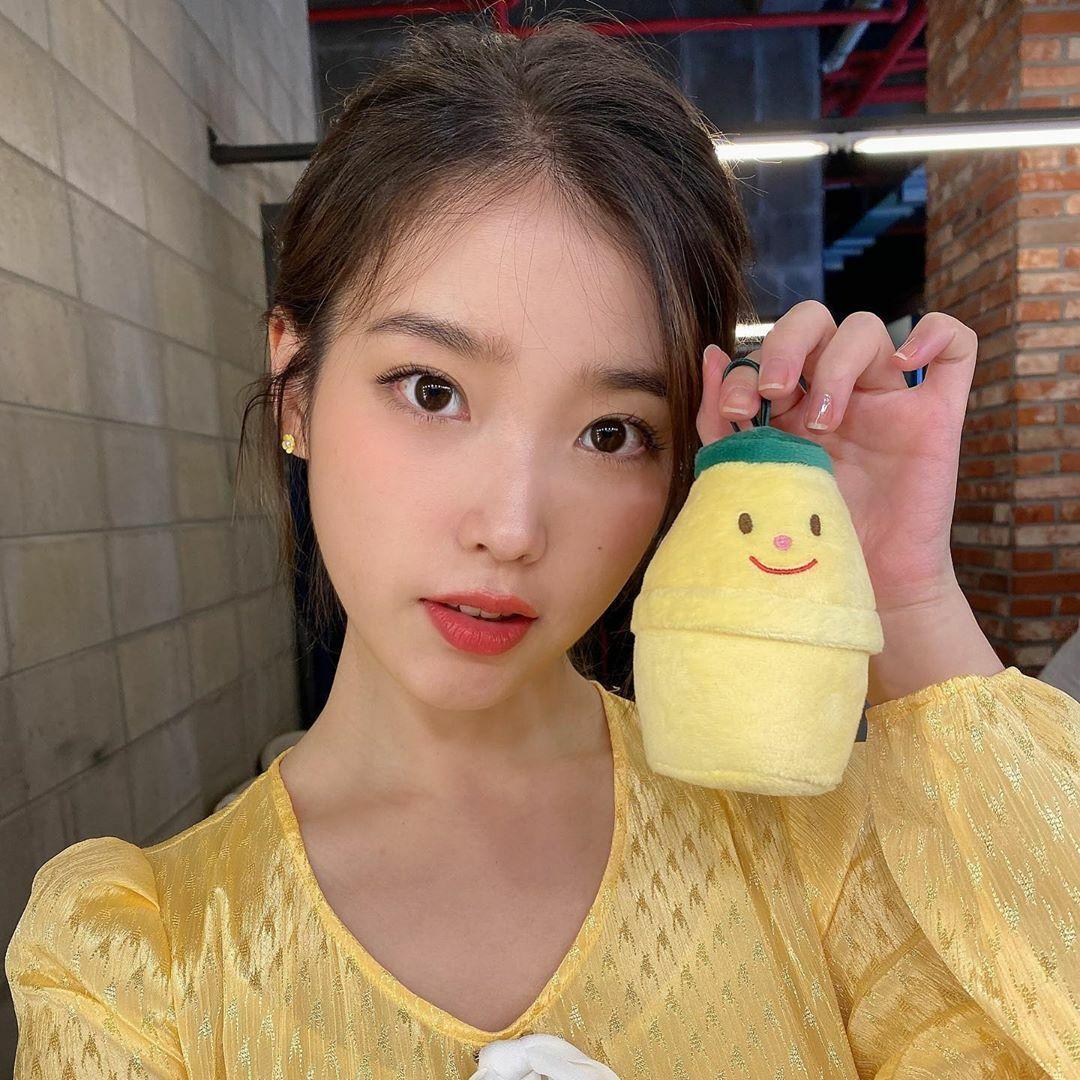 IU mặc váy vàng tông xuyệt tông với... móc khóa bông hình sữa chuối.