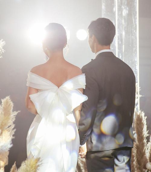 Phần vai váy được làm từ vải xếp nếp, tạo thành một chiếc nơ lớn ở phía sau làm điểm nhấn. Để giữ phong cách thanh lịch, Viên Minh hạn chế trang sức, không cài khăn voan. Kiểu đầm như bà xã Công Phượng có giá thuê chỉ khoảng 35 triệu đồng.