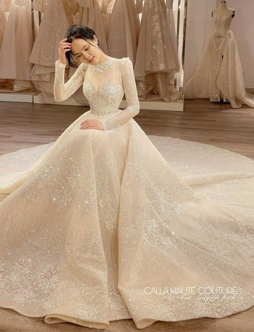 Phân đuôi váy bồng bềnh, phù hợp với phong cách và biệt danh 'công chúa béo' của Quỳnh Anh. Những phụ kiện như vương miện, voan trùm đầu, đai đính đá,... đều được chế tạo một cách tỉ mỉ, tinh tế, tôn lên vẻ đẹp ngọt ngào, rạng rỡ của cô dâu.