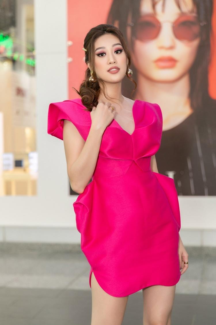Khánh Vân mặc đầm cocktail hồng. Hình ảnh của cô có phần mờ nhạt sau đăng quang.