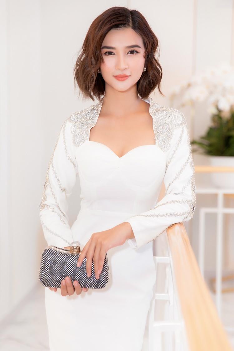 Kim Tuyến mặc đầm trắng thanh lịch của NTK Hà Thanh Huy, tái xuất tại một sự kiện thời trang tối 30/6 tại TP HCM. Người đẹp sử dụng clutch đính đá, tạo điểm nhấn cho tổng thể.