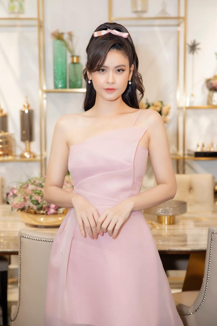 Trương Quỳnh Anh mặc đầm lụa mỏng ôm sát, gam màu hồng đến mừng stylist Kan Hí lên chức ông chủ tại TP HCM. Cô cột tóc cao, đeo khuyên tai ngọc trai.