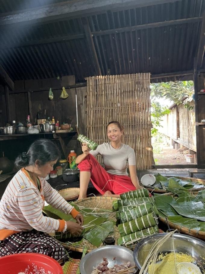 HHen Niê cùng gia đình gói bánh tét. Cô để mặt mộc, mặc đồ giản dị, khoe khoảnh khắc đoàn viên. Năm nay, cô không nhận show dịp Tết để có thời gian ở bên gia đình.